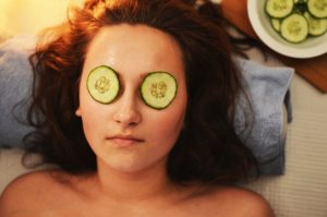 woman with sliced cucumbers on eyes