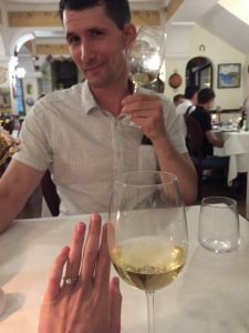 hand with engagement ring and man with wine