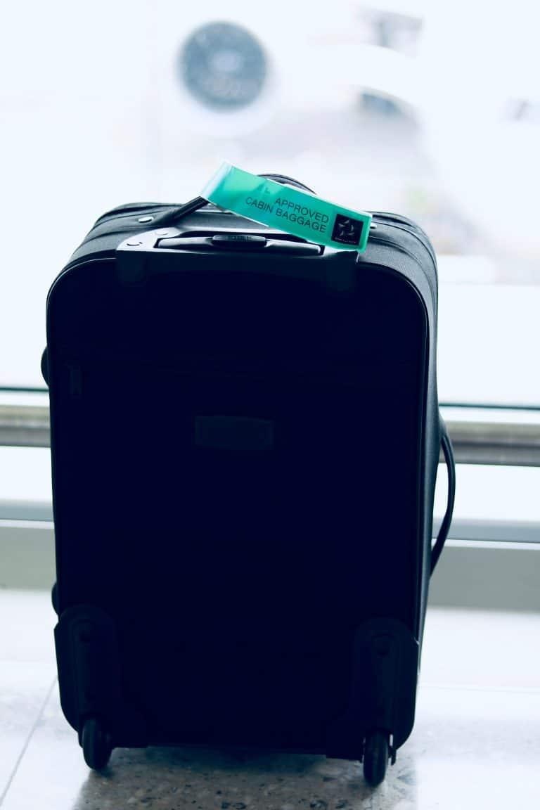 Black Luggage Bag Near Wall