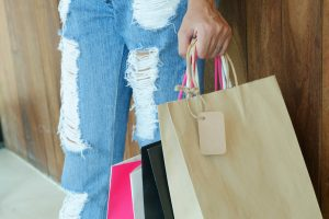 woman with ripped jeans holding shopping bags