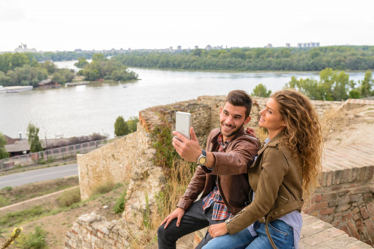 Young handsome couple taking a selfie near the river