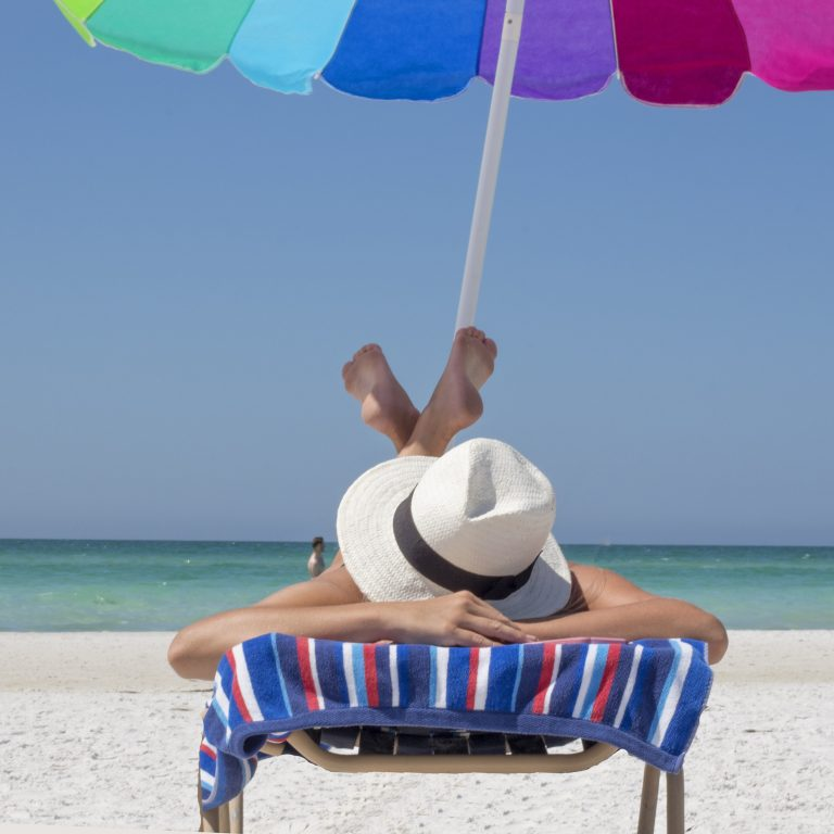 Woman with hat laying on towel under umbrella at beach