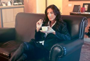 Woman in black blazer holding teacup while sits on black sofa