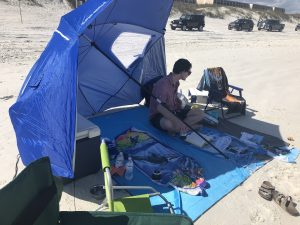 man sitting on beach towel under umbrella at beach