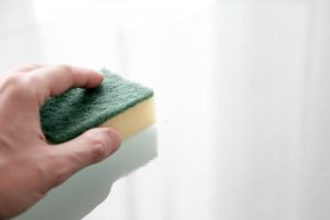 Hand using Sponge on White Surface