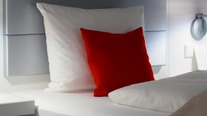 white bed with white and red pillow