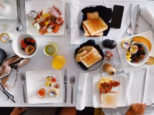 spread of breakfast food on white tablecloth