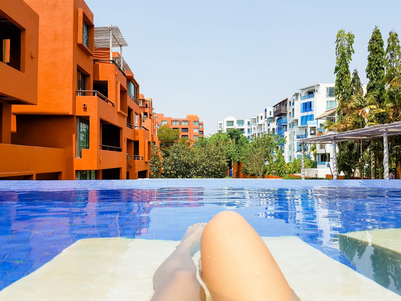 Woman lying on a lounger by the pool at the hotel. Girl at trave