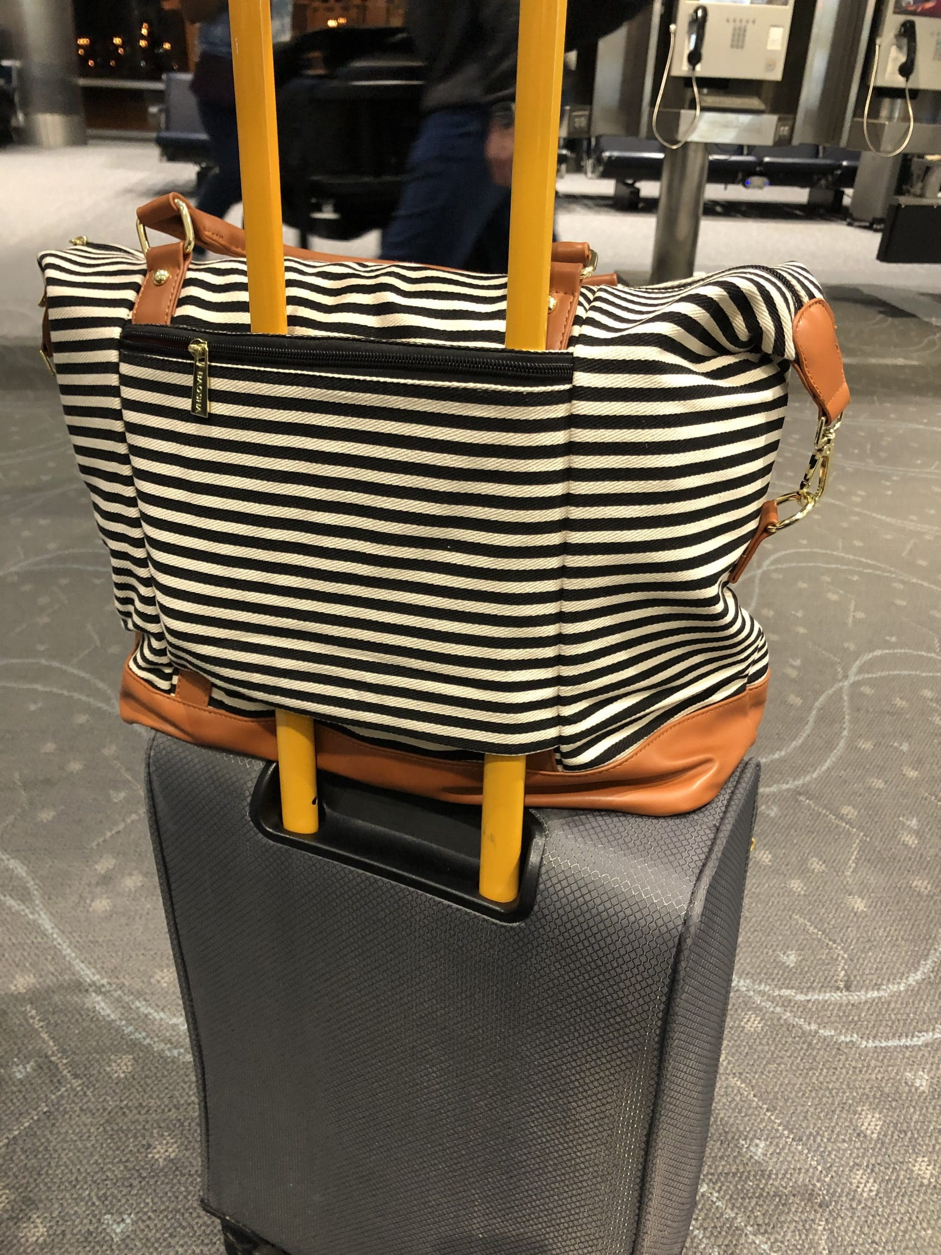 striped bag on top of suitcase