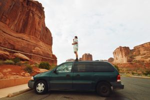 Man standing on top of green mini van