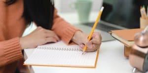 girl writing in orange journal