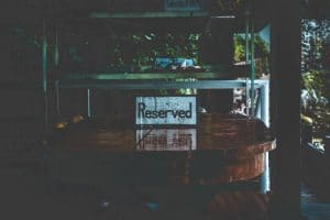 White Reserved Sign on Brown Wooden Table
