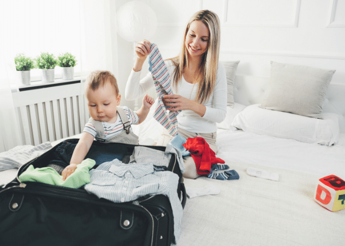 woman packing suitcase with baby
